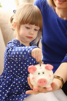 Brazo de niña pequeña poniendo monedas de dinero pin en retrato de ranura de lechón cara rosa feliz.