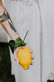 Brazo tatuado sosteniendo un limón fresco
