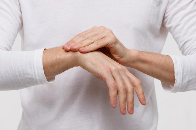 Brazos de hombre sosteniendo su muñeca dolorosa, síndrome del túnel carpiano, artritis