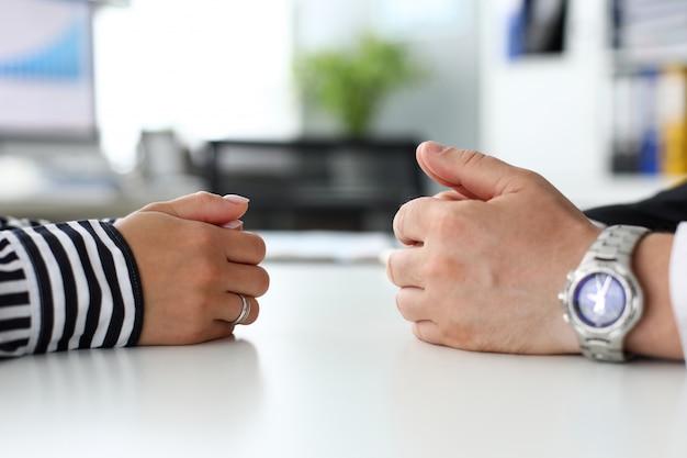 Brazos masculinos y femeninos acostados en el lado opuesto de la mesa comunicando