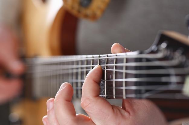 Brazos masculinos que tocan la guitarra eléctrica de forma clásica