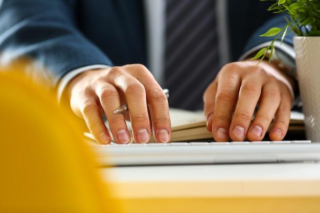 Brazos masculinos en traje escribiendo en teclado plateado