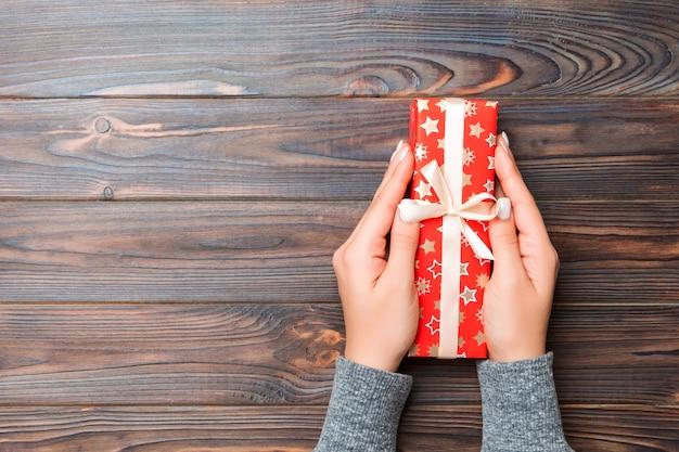 Brazos de mujer con caja de regalo con cinta de color en la mesa de madera oscura, vista superior copia espacio