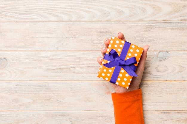 Brazos de mujer con caja de regalo con cinta de color en la mesa de madera rústica amarilla, vista superior