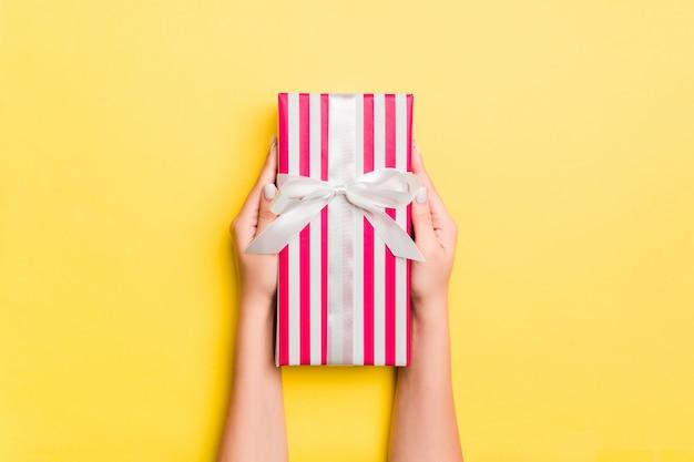 Brazos de mujer con caja de regalo con cinta de color sobre fondo amarillo de mesa