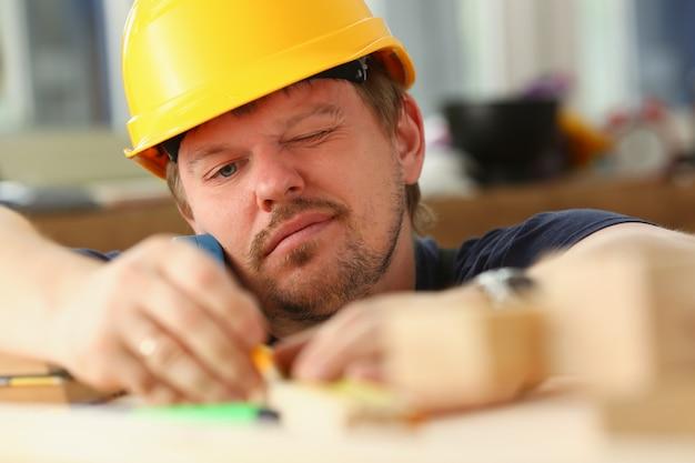 Brazos de trabajador midiendo barra de madera