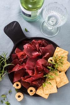 Bresaola italiana servida en rodajas en una bandeja sobre una mesa con vino blanco, galletas, grissini y taralli con hierbas aromáticas sobre un mantel festivo de lino azul.