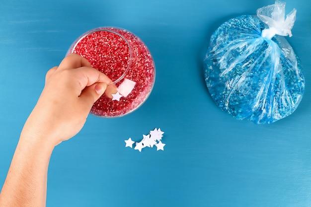 Bricolaje el 4 de julio, jarrón de frascos de vidrio y arroz coloreado. bandera estadounidense, rojo, azul, blanco.