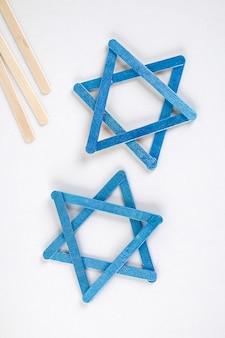 Bricolaje. decoración de janucá. estrella de david de palitos de helado sobre una mesa de madera blanca. diy sobre hanukkah.