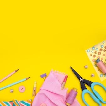 Bricolaje. suministros de artesanía multicolor y herramienta en amarillo.