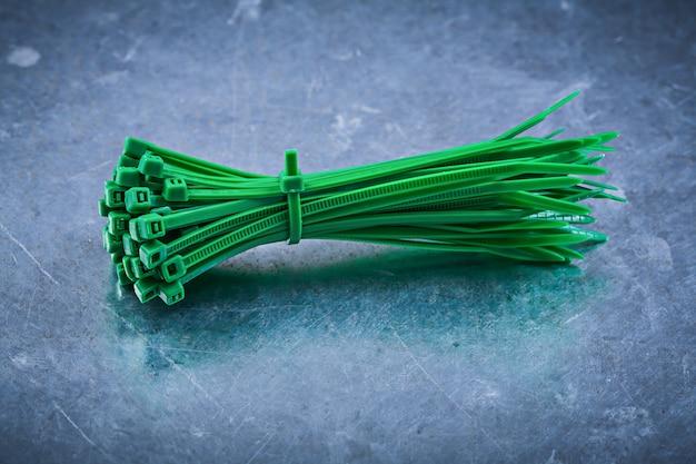 Bridas de plástico autoblocantes de plástico verde sobre mesa metálica