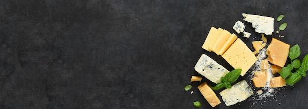 Brie, queso azul, parmesano y albahaca sobre una mesa de hormigón negro.