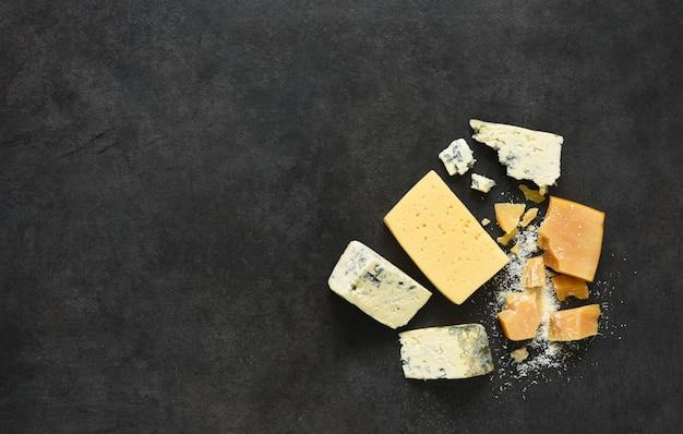 Brie, queso azul, parmesano sobre una mesa de hormigón negro.