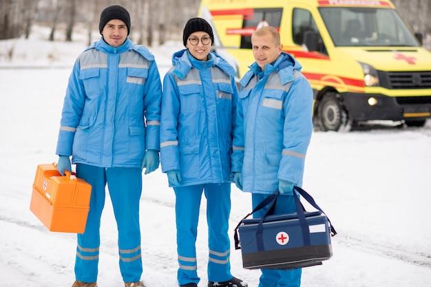 Brigada de jóvenes paramédicos en ropa de trabajo azul y guantes sosteniendo botiquines de primeros auxilios mientras está de pie al aire libre
