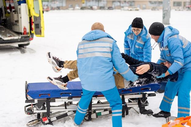 Brigada de paramédicos en uniforme de invierno llevando y poniendo al hombre inconsciente en una camilla para llevarlo al coche de la ambulancia