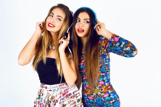 Brigit retrato de moda de dos mejores amigas dj girls, vistiendo vestidos, auriculares y escuchando su música favorita.