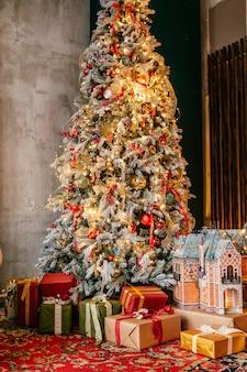 Brillante árbol de navidad en una habitación con alfombra roja con muchos regalos