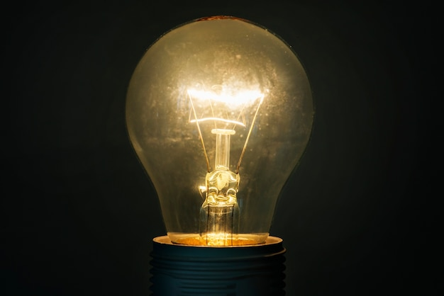 Brillante bombilla de luz de cristal sobre fondo oscuro