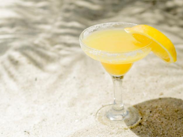 Brillante cóctel naranja fresco en la arena