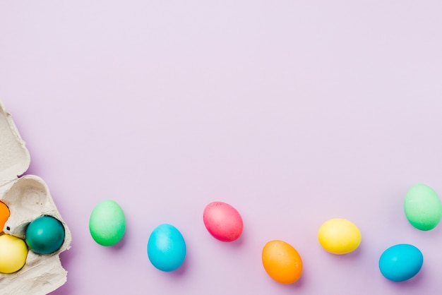 Brillante colección de hileras de huevos de colores cerca del contenedor