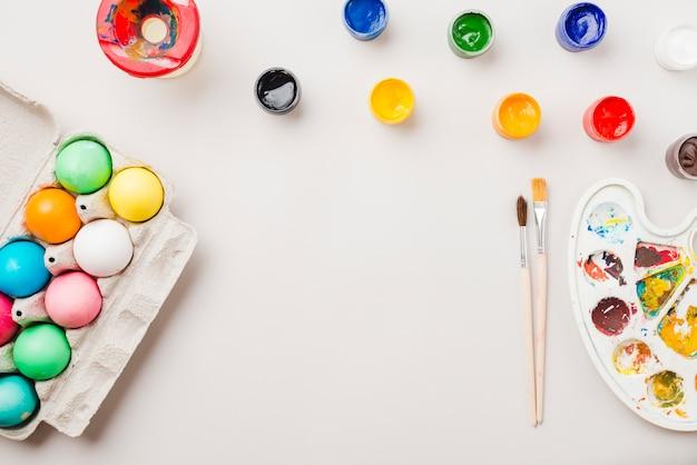 Brillante colección de huevos de colores cerca de un recipiente cerca de pinceles, acuarelas y paleta