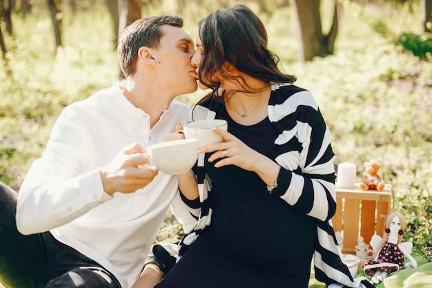 Brillante y feliz mujer embarazada sentada en el parque con su marido y bebiendo un té