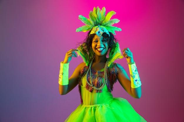 Brillante. hermosa mujer joven en carnaval, elegante disfraz de mascarada con plumas bailando en la pared degradada en neón. concepto de celebración navideña, tiempo festivo, baile, fiesta, diversión.
