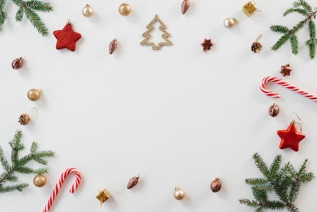 Brillante marco de navidad de abeto, marrón y oro decoraciones de navidad, mentas sobre un fondo blanco. copyspace vacaciones de invierno, año nuevo.