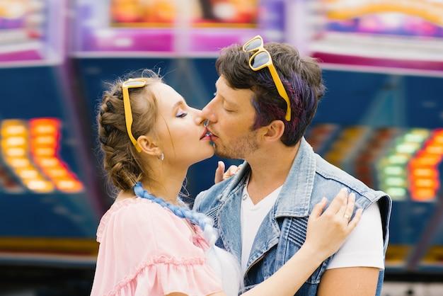 Brillante pareja de un chico y una chica están descansando en un parque de diversiones.