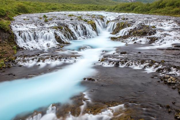 Brillante potente cascada de bruarfoss en islandia con agua cian.