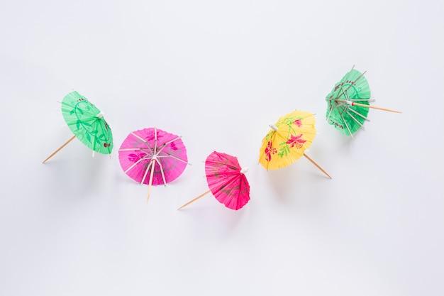 Brillantes cócteles paraguas en mesa blanca