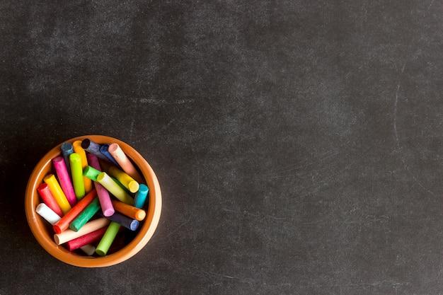 Brillantes crayones pastel se encuentran en un recipiente de cerámica