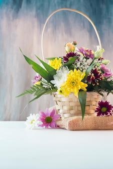 Brillantes flores en canasta colocadas en trozo de arpillera.