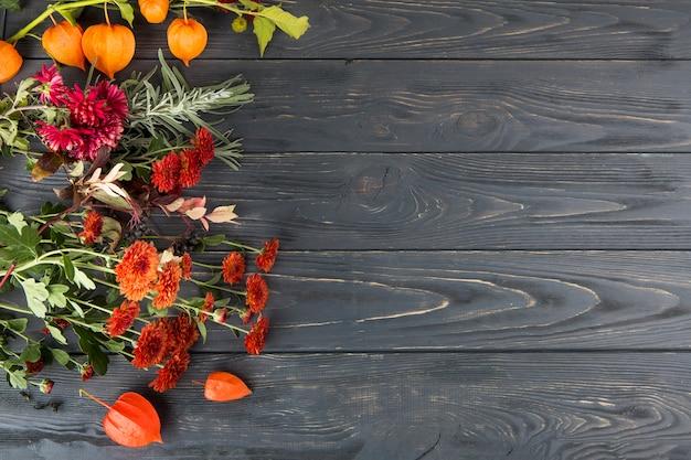 Brillantes flores esparcidas sobre mesa de madera.