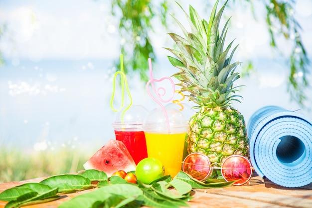 Brillantes jugos frescos y saludables, frutas, piña, sandía. gafas de sol estera de yoga en el mar