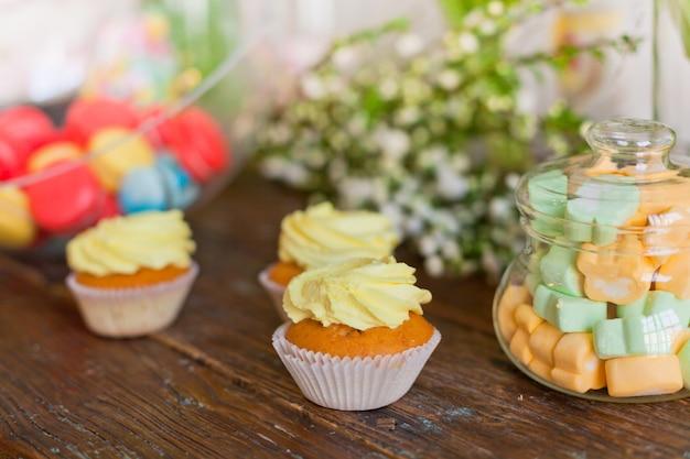 Brillantes macarons y cupcakes en una mesa