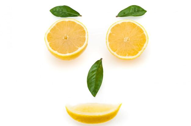 Brillantes rodajas de limón y hojas verdes en forma de cara.