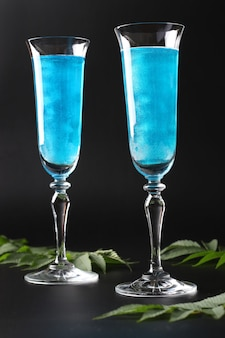 Brillo comestible brillo vino azul espumoso en dos vasos altos sobre fondo negro