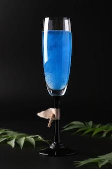 Brillo comestible brillo vino azul espumoso en vaso alto sobre fondo negro. formato vertical. de cerca