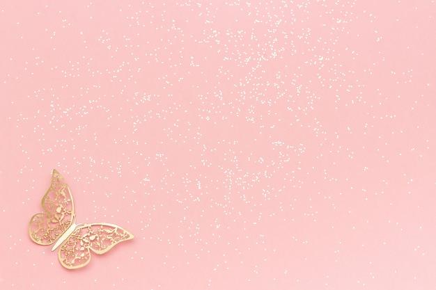 Brillo de destellos y mariposa de tracería de oro sobre fondo rosa pastel de moda. fondo festivo, plantilla