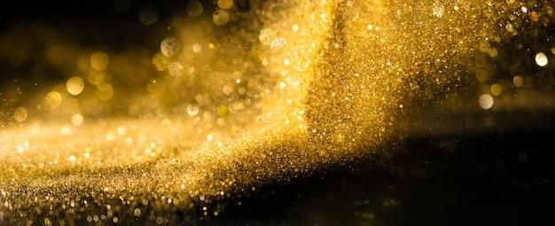 El brillo enciende el fondo del grunge, el brillo del oro defocused fondo abstracto de las luces del centelleo.