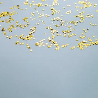 Brillo de estrellas doradas brillantes o confeti sobre fondo gris con espacio de copia
