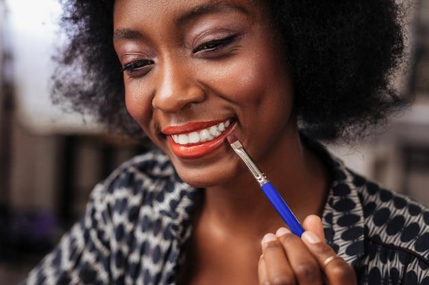 Brillo de labios coral. increíble mujer con cabello rizado que parece feliz mientras se prueba el brillo de labios coral.
