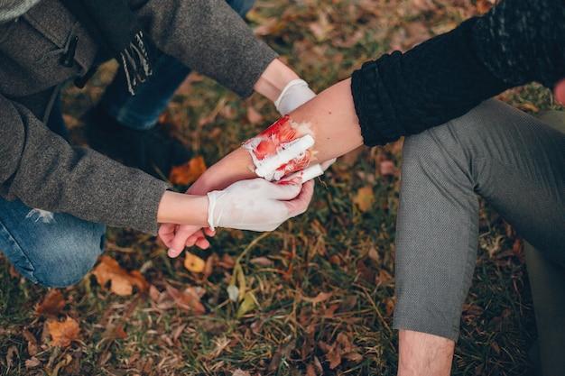 Brindar primeros auxilios en el parque. hombre vendado brazo lesionado. guy ayuda a un amigo.