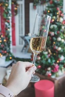 Brindis con copa de champán en mano femenina. celebración de la víspera de año nuevo. concepto de fiesta, bebidas, vacaciones, personas y celebración. decoración de champán y año nuevo. fiesta con vino espumoso