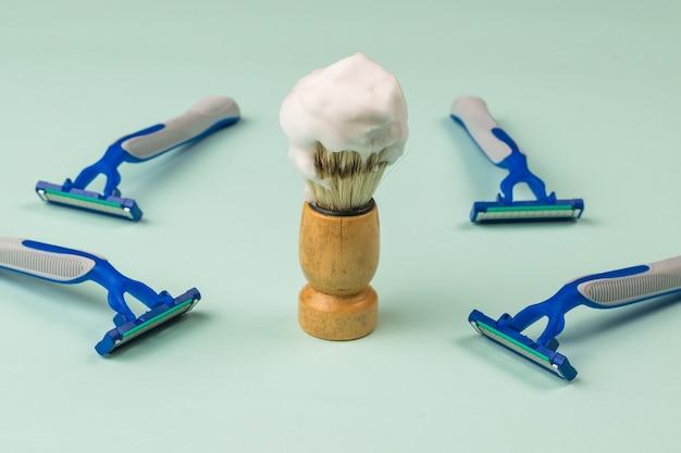 Una brocha de afeitar con espuma de afeitar y cuatro maquinillas de afeitar desechables sobre una superficie azul