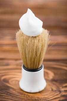 Brocha de afeitar sintética con sobre mesa de madera.