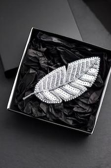 Broche bordado con cuentas de semillas en forma de pluma en una caja de regalo negra sobre fondo negro