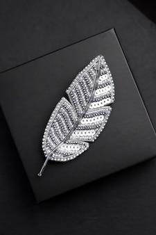 Broche bordado con cuentas de semillas en forma de pluma sobre fondo negro