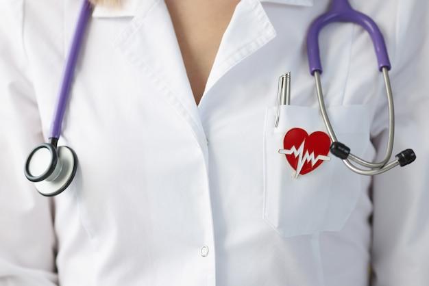 Broche en forma de corazón colgando de uniforme de doctor closeup